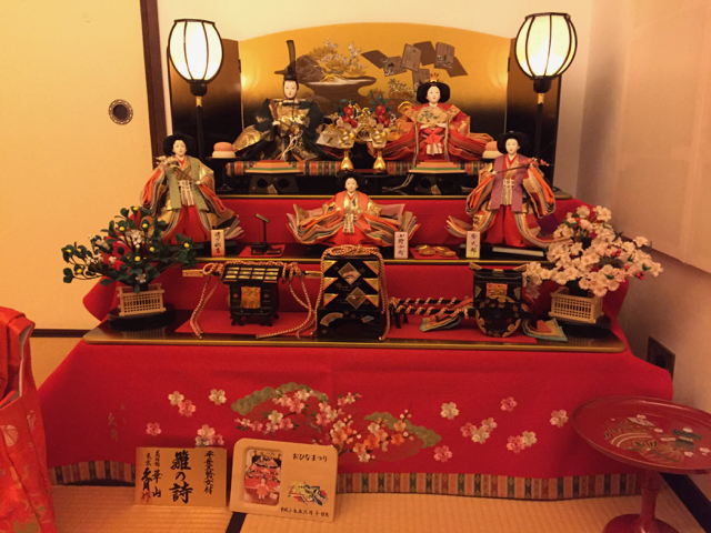 The Hina dolls: a princess and prince on the top shelf, with three female attendants on the shelf below, and an ox-drawn carriage, palanquin, and treasure box on the bottom shelf. All the dolls are dressed for the Heian period.