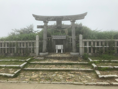 A stone torii in front of an earth mound with grass and trees growing on it.